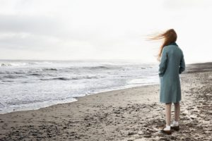 Girl (10-12) looking out to sea, rear view (Digital Composite)